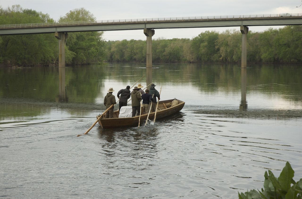 Caption: Andrew Shaw and crew poling upstream in a batteau on the James