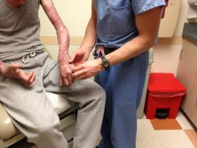 Caption: Resident Brian Drolet examines a patient's burned arm., Credit: Kristin Gourlay