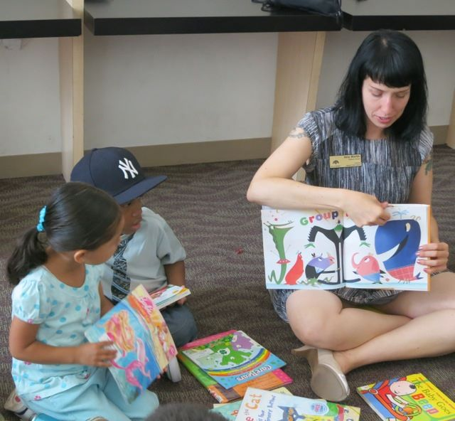 Caption: Oakland Public Library children's librarian reads at the Eastmont Social Service Agency, Credit: Holly J McDede