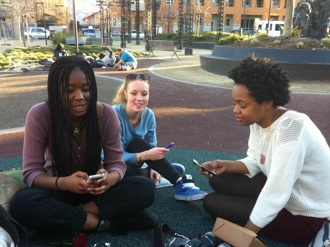 Caption: Three high school students in Oakland, Calif., swap photos using Snapchat. (Ike Sriskandarajah)