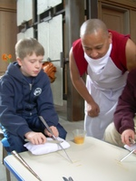 Caption: A young apprentice tries his hand at making a mandala.