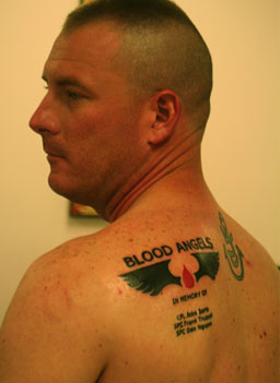 Caption: Medic Clint McCullough shows off his memorial tattoo with the name of his unit, and the names of three friends who died., Credit: Michael May