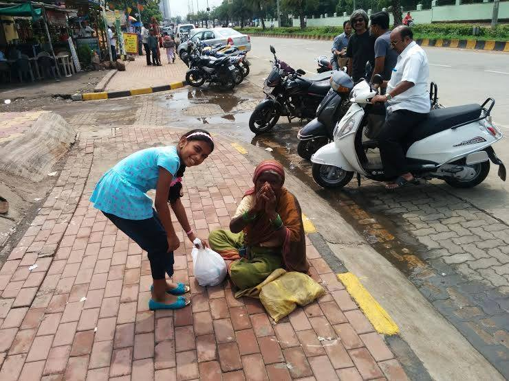 Caption: Shiva Shankar from Hyderabad gets his niece Vaishnavi from Pune to donate rice to a woman who works there