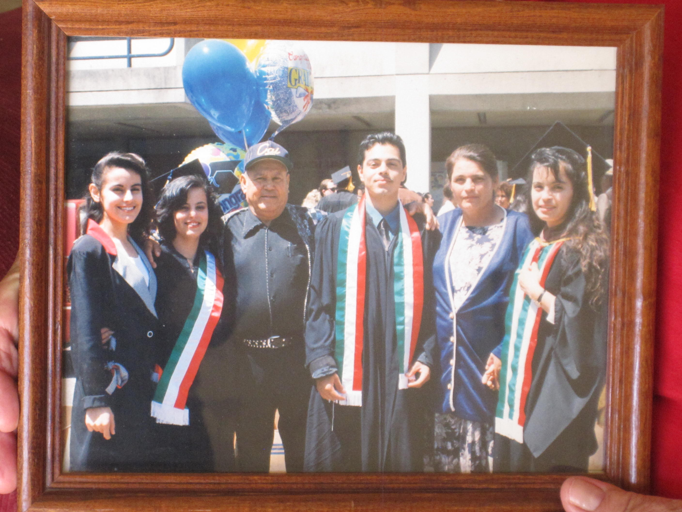 Caption: Maria and Fabian Ramirez graduated from UC Berkeley on the same day that their older sister Gloria received her master's degree. From left: Angela, Maria, father Filemon, Fabian, mother Lucila, and Gloria. , Credit: Zaidee Stavely / Radio Bilingüe