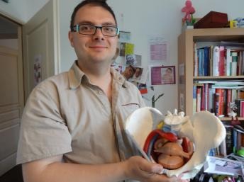 Caption: Midwife Nicolas Dutriaux holds a model of a pelvis he uses with patients., Credit: Sarah Elzas