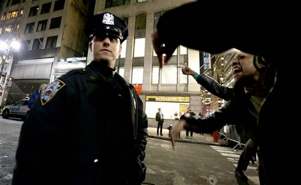 Caption: NYC Police Officer during protest, Credit: Miami Herald