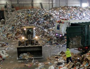 """Caption: Trucks dump their loads of single-stream recycling on the """"tip floor"""" at Resource Management's Materials Recovery Facility (MRF) in Earth City, Mo., Credit: Véronique LaCapra"""