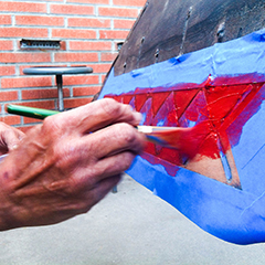 Caption: A Ti'at Society member paints a red ocher detail onto Moomat Ahiko's side., Credit: Stephanie Case