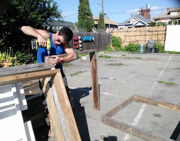Caption: Luke Iseman puts together raised bed garden containers, Credit: Chris Hambrick