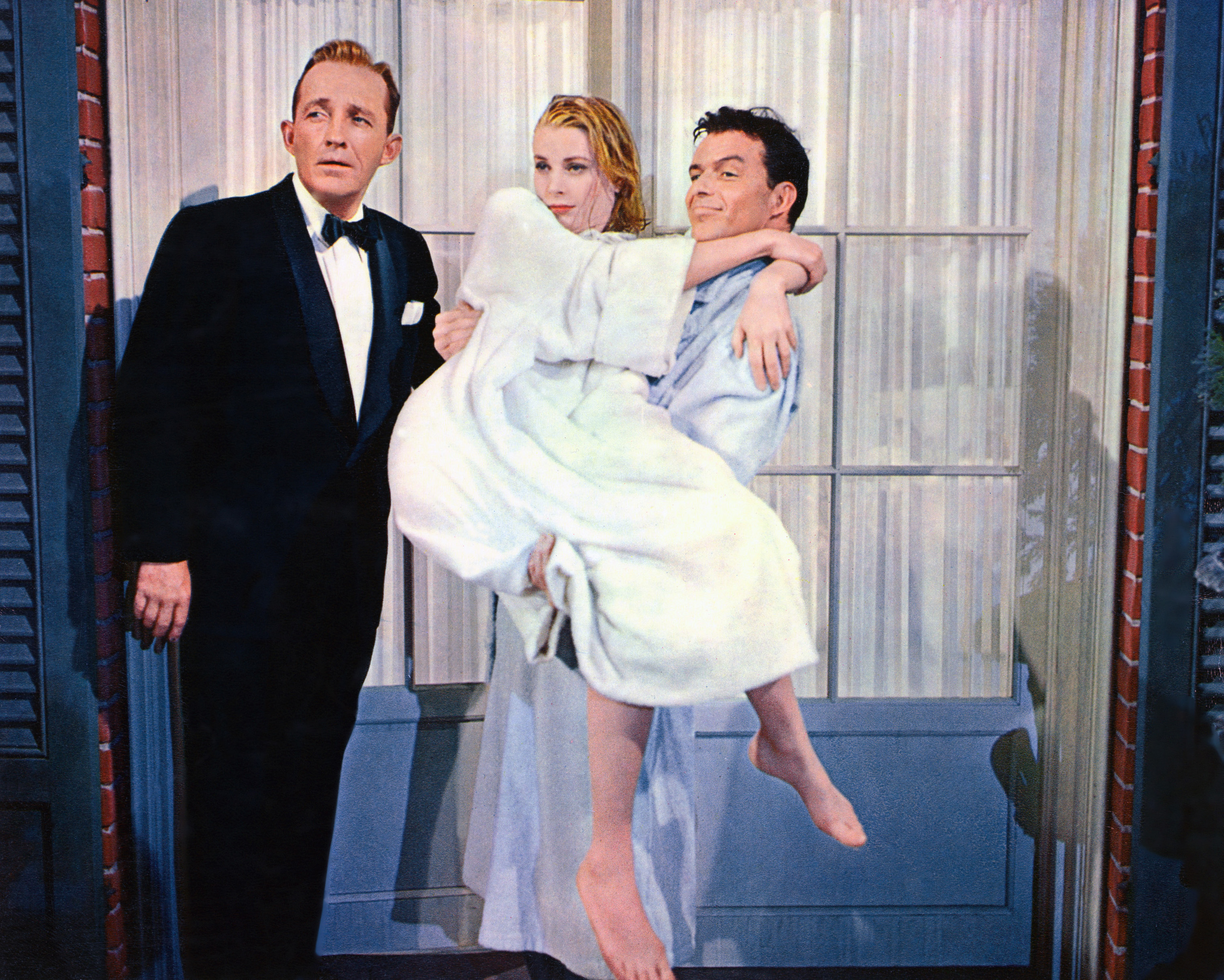 Caption: Bing Crosby, Grace Kelly carried by Frank Sinatra in a publicity still from the film, 'High Society', 1956, Credit: Silver Screen Collection/Getty
