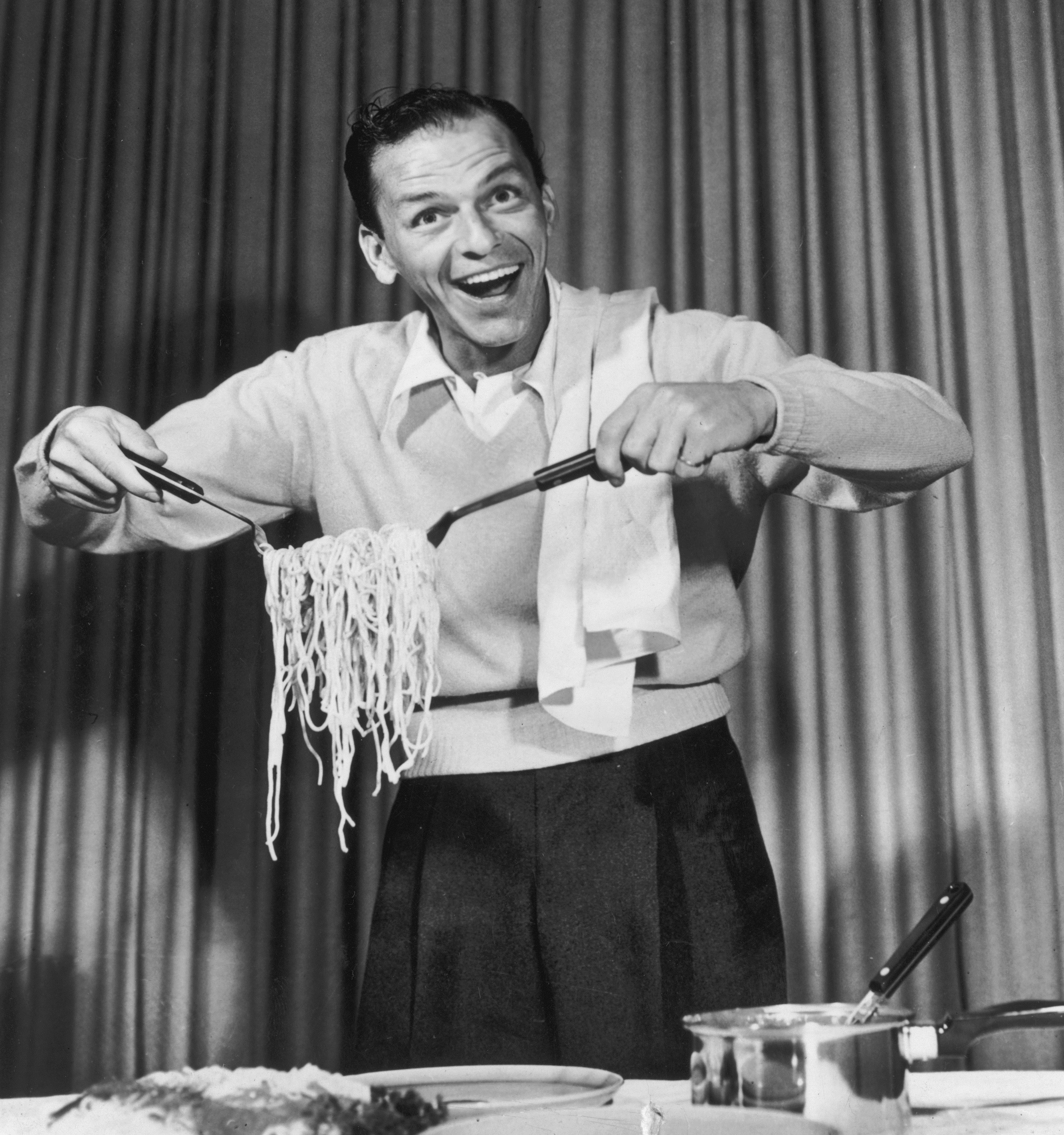 Caption: American actor and singer Frank Sinatra clowning around with spaghetti for an EKCO products commercial on the set of CBS-TV's, 'The Frank Sinatra Show.' , Credit: CBS Photo Archive/Getty