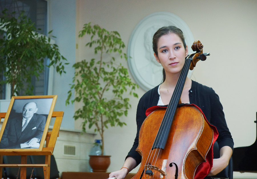 Caption: Cellist Meta Weiss performs next to a portrait of Vissarion Shebalin during her research trip to Moscow. Weiss is currently a professor at Queensland Conservatorium in Brisbane, Australia