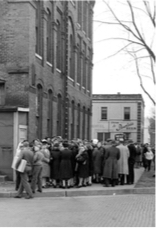 Caption: Waiting in line for nylon stockings at Stansfield Knitting Mills and ration stamps.