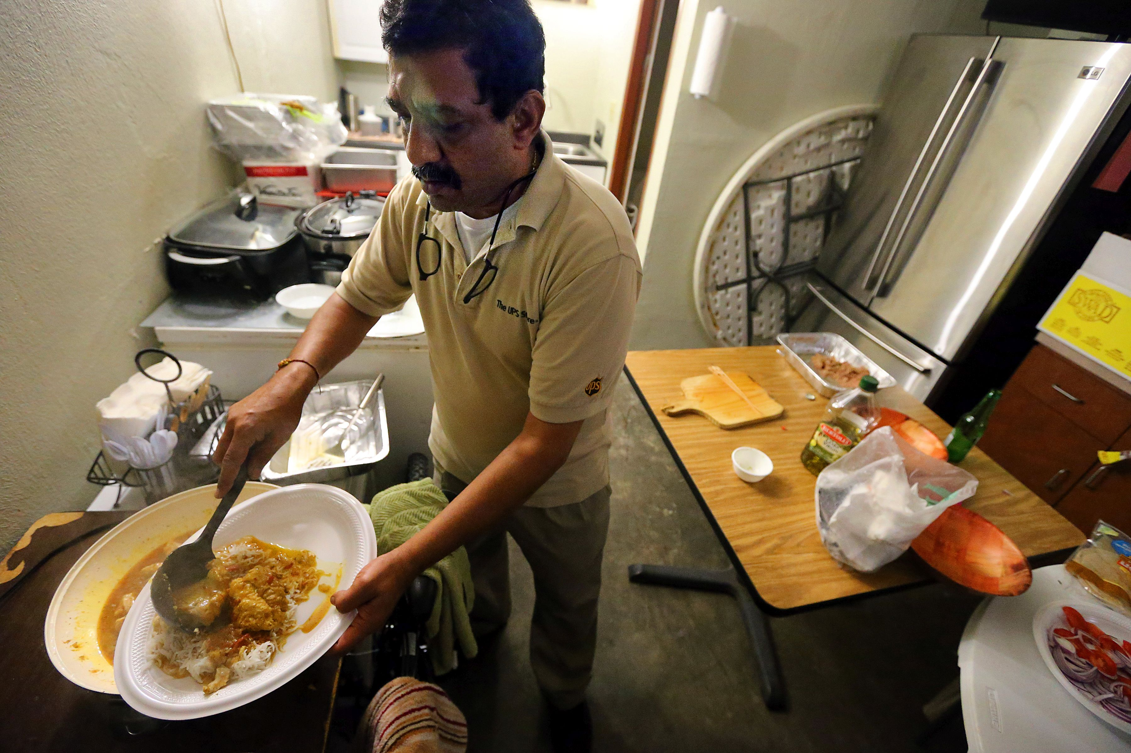 Caption: Vimal Patel cooks inside -- and outside -- a room in the Day's Inn he operates in North Charleston. , Credit: Photo by Wade Spees for the Post & Courier.