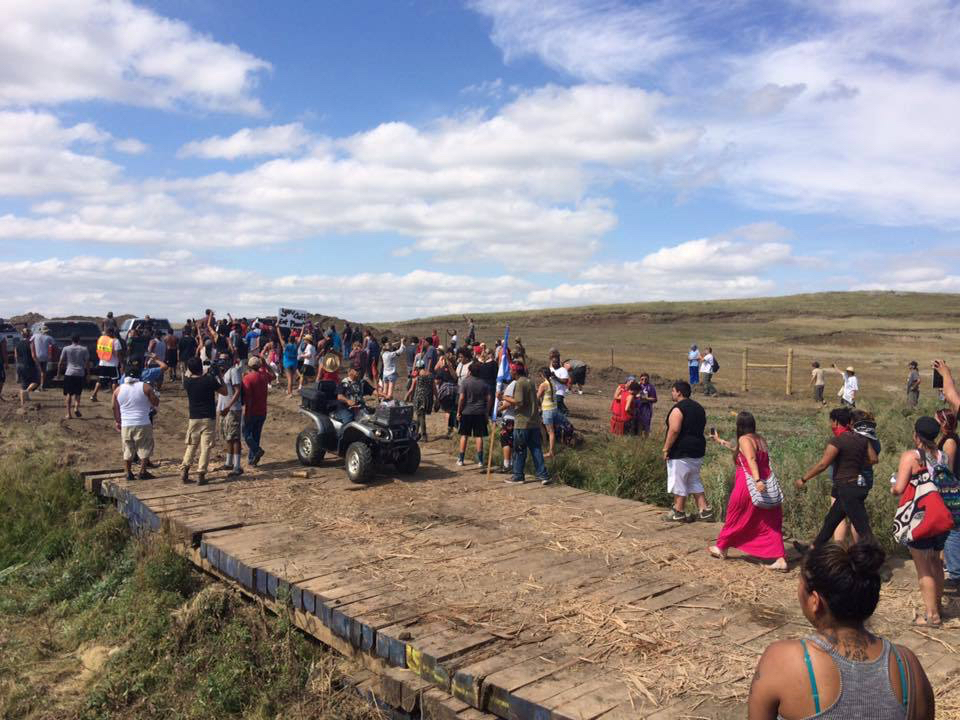 "Caption:  September 3, shortly before protestors clashed with private security. Reyna Crow writes "" I took it as I was approaching the end of the wooden bridge there where the women linked arms a few minutes later."", Credit: Reyna Crow"