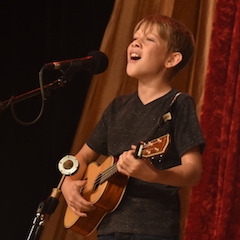 Caption: WoodSongs Kid Ian Shaw performs.
