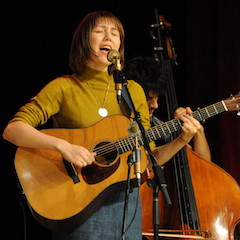 Caption: IBMA guitar player Molly Tuttle on the WoodSongs Stage.