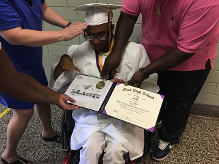 Caption: Veronica Volk/WXXI News, Credit: Akin Johnson holds his credential during the East High School commencement in June 2017.