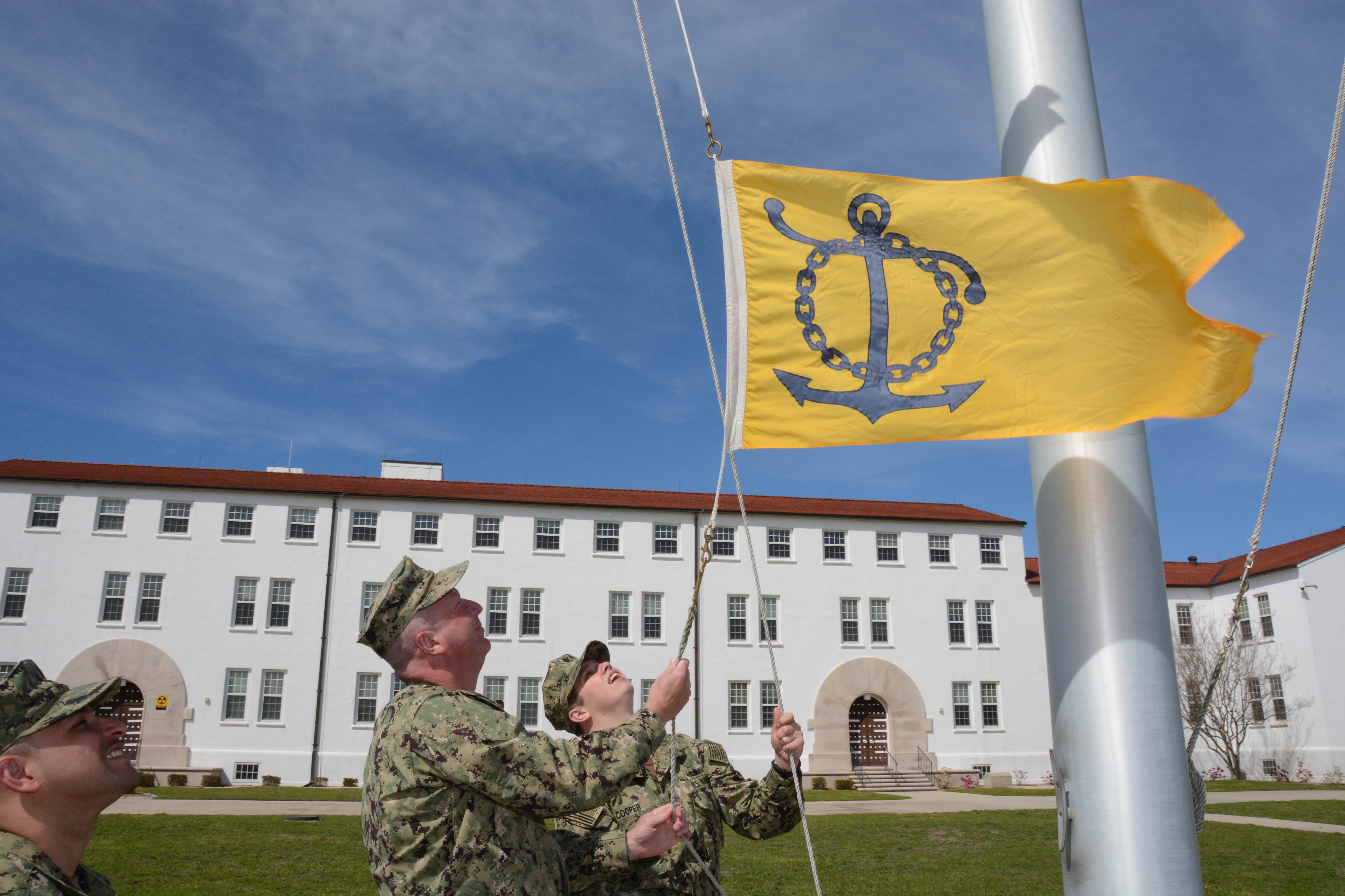 Caption: Sailors at Naval Air Station Pensacola, Fla. raise a flag to recognize the station's success at retaining personnel. The Navy recognizes units that do a good job keeping sailors in the service., Credit: Greg Mitchell / U.S. Navy