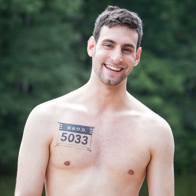 Caption: Justin poses with the tattoo that you got for his twentieth birthday, representing the cross country bib that was taken away from him in 2010., Credit: (c) Janel Semonasky, 2017
