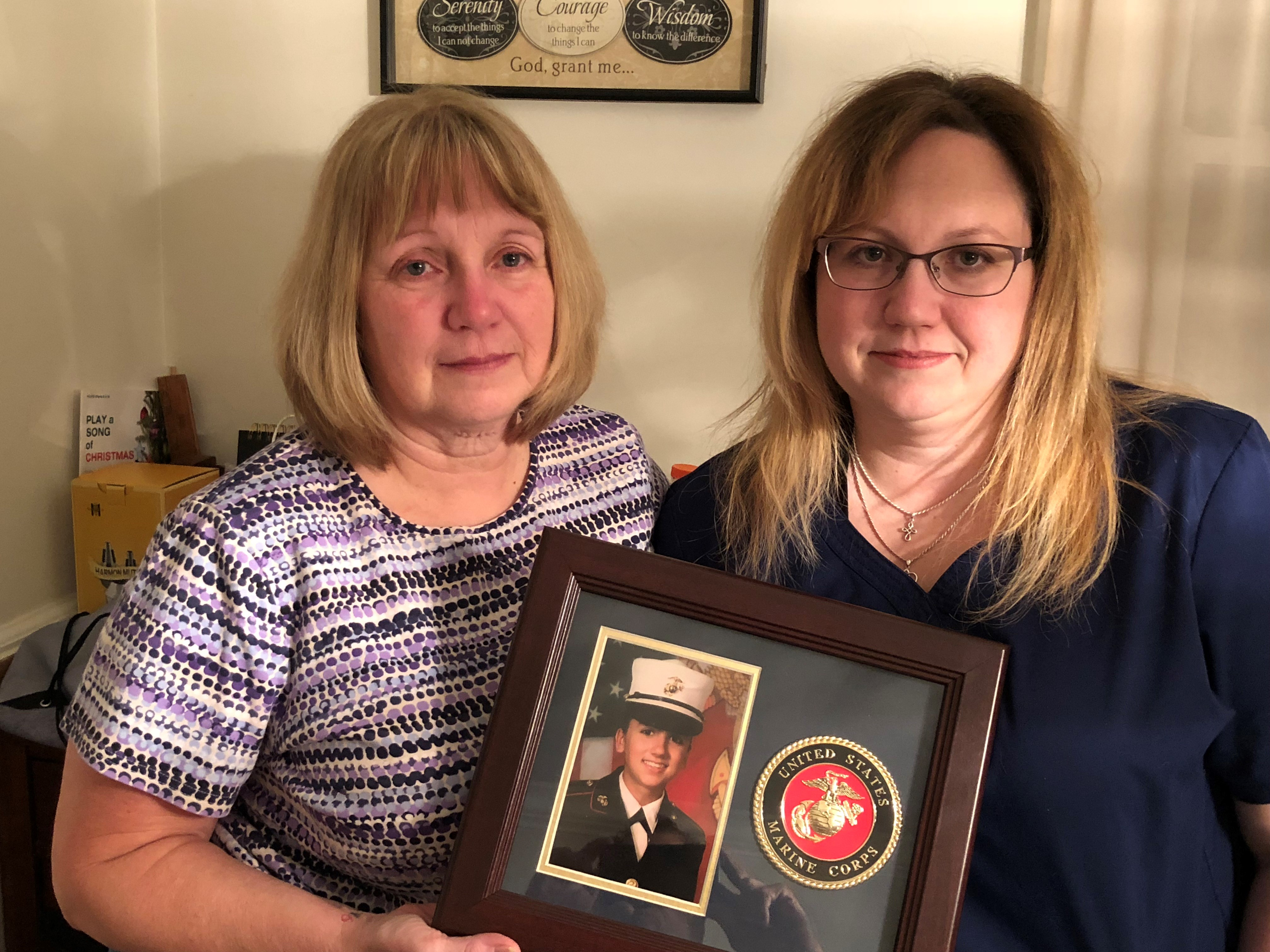 Caption: Deana Martorella Orellana's mother, Laurel Martorella (left), and Orellana's sister, Robin Jewell, hold her Marine Corps photo. Orellana killed herself a year after leaving the Marines. She had agreed to undergo counseling the day she died., Credit: Jay Price/American Homefront