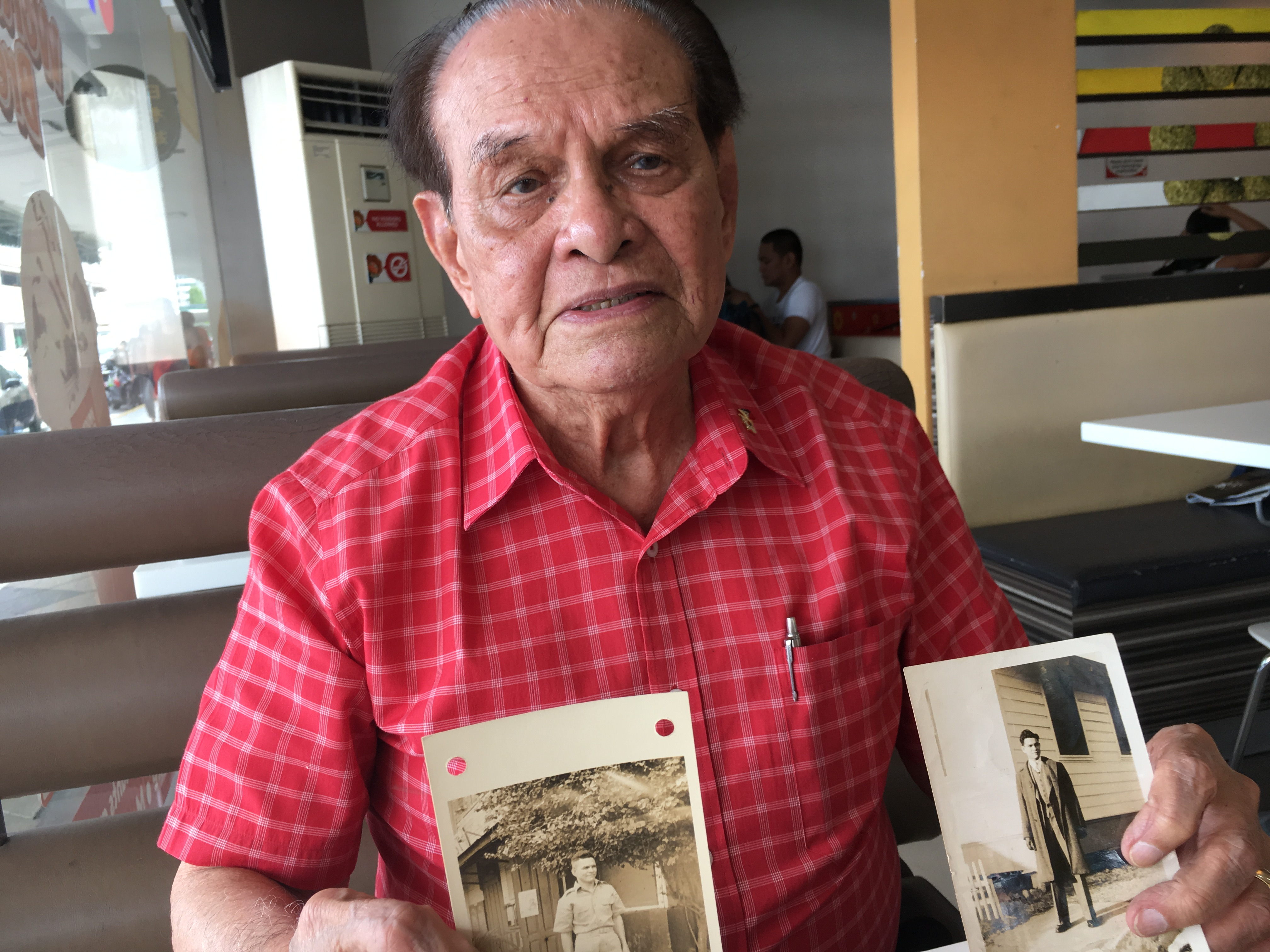 Caption: Maximo Purisima Young, 97, displays photographs from his military service. He helped transport supplies and troops in World War II, then fought as a guerilla alongside American soldiers., Credit: Dorian Merina/American Homefront