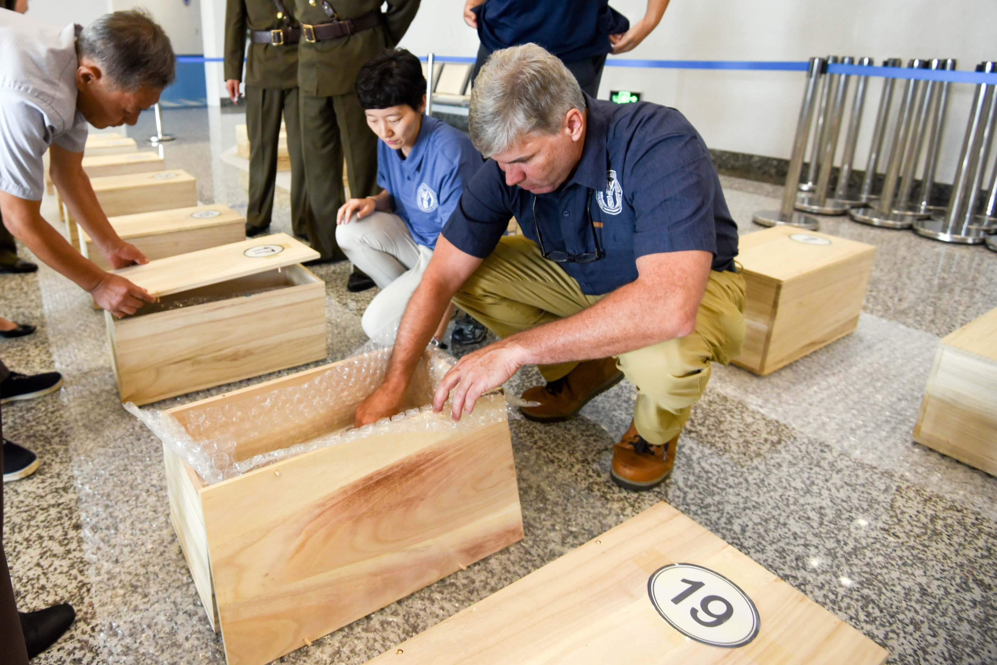 Caption: U.S. Defense Department forensic anthropologists in Wonsan, North Korea examine the contents of boxes containing the possible remains of U.S. MIAs July 27, 2018., Credit: David Marshall / U.S. Army