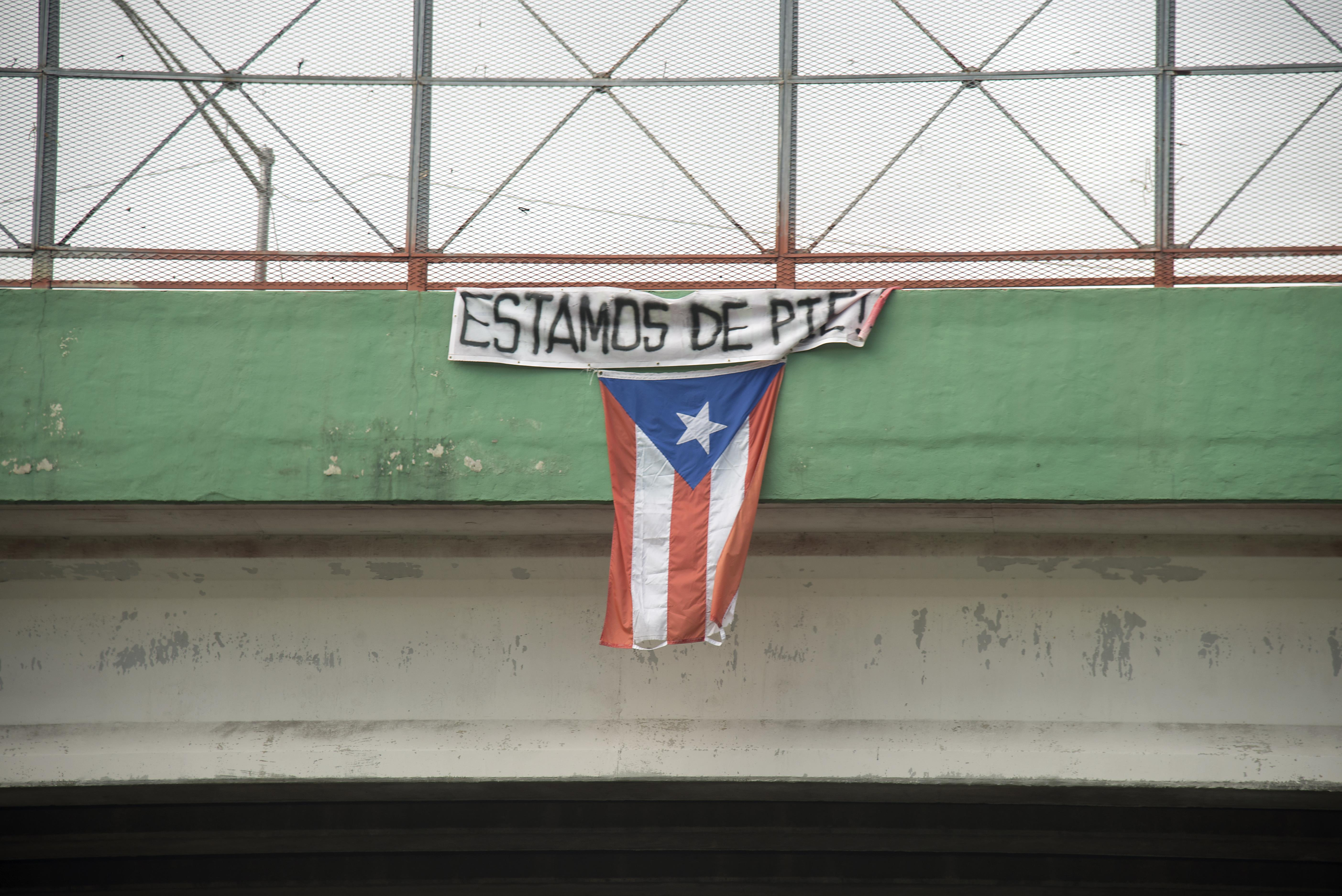 "Caption: A flag hangs from a highway overpass that reads ""Estamos de pie,"" in Caguas, Puerto Rico, Oct. 2, 2017. , Credit: Airman 1st Class Caleb Nunez"