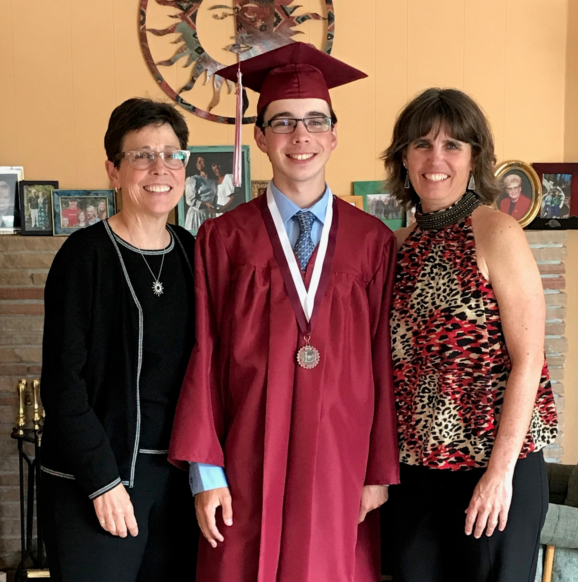 Caption: Reporter Wyatt Barmore-Pooley and his moms Becky and Lisa after his high school graduation