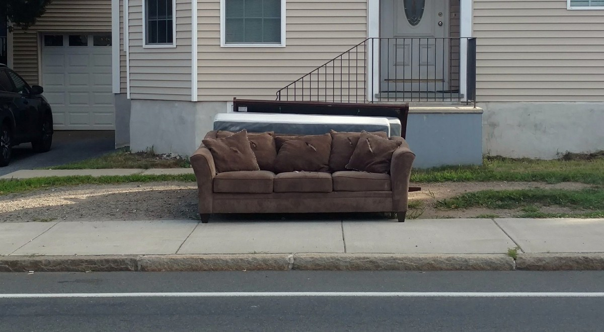 """Caption: A sofa and mattresses on the street in front of an apartment building. """"Sofa Free, and throw in 2 box springs"""", Credit: walknboston is licensed under CC by 2.0."""