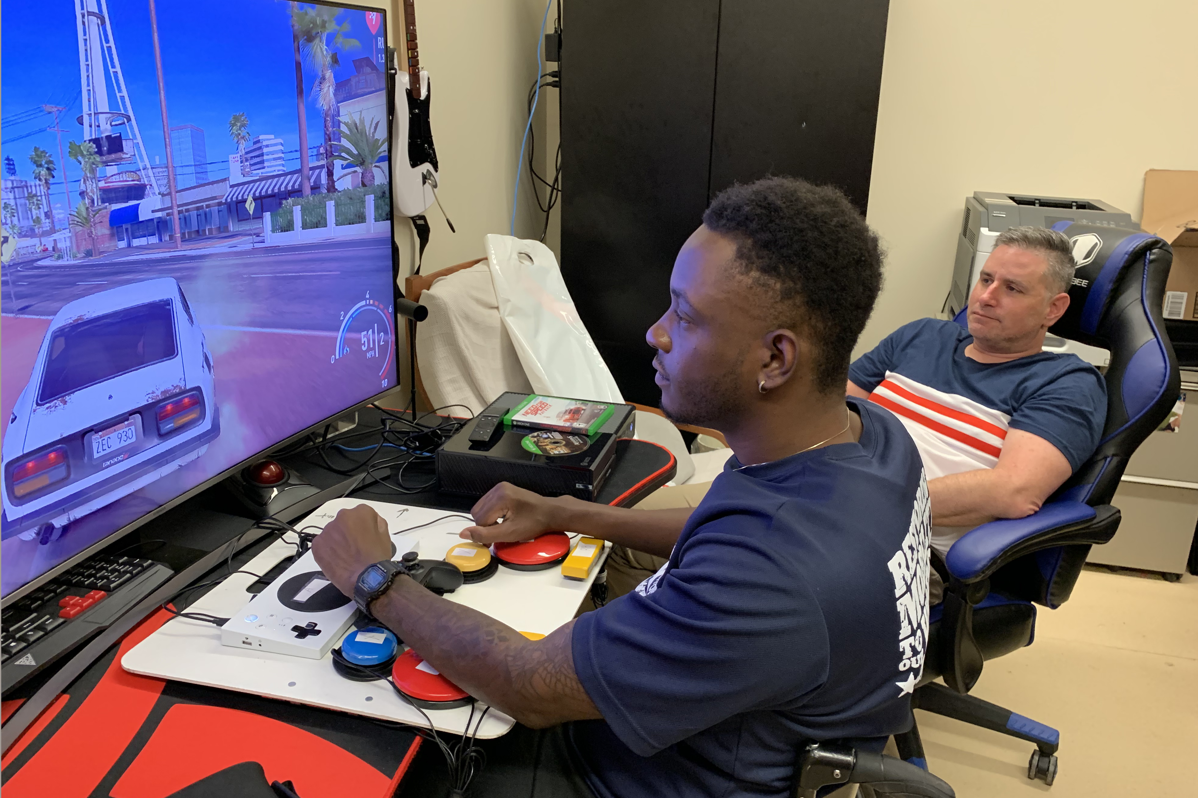 Caption: Army veteran Mike Monthervil (left) uses an adaptive controller to play video games as his VA recreational therapist Jamie Kaplan watches., Credit: Stephanie Colombini/American Homefront