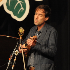 Caption: Andrew Bird whistling on the WoodSongs Stage.