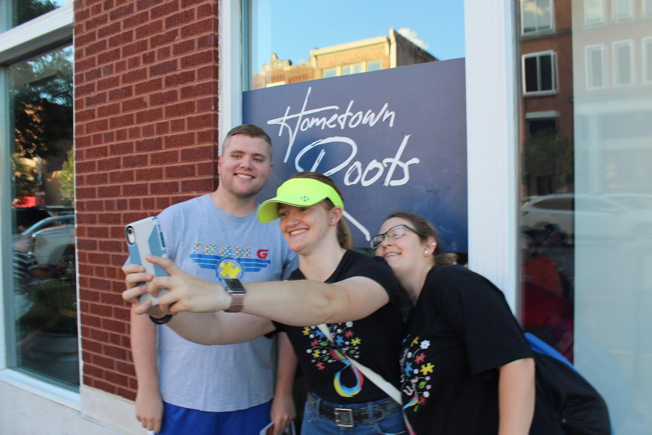 Caption: Henderson, Ky., was the scene of a scavenger hunt by members of a social group geared toward adults with autism. (L to R) Jesse Hopgood, Rose Schriener and Hannah Hall pose for a selfie as part of the hunt., Credit: ISAIAH SEIBERT, SIDE EFFECTS PUBLIC MEDIA