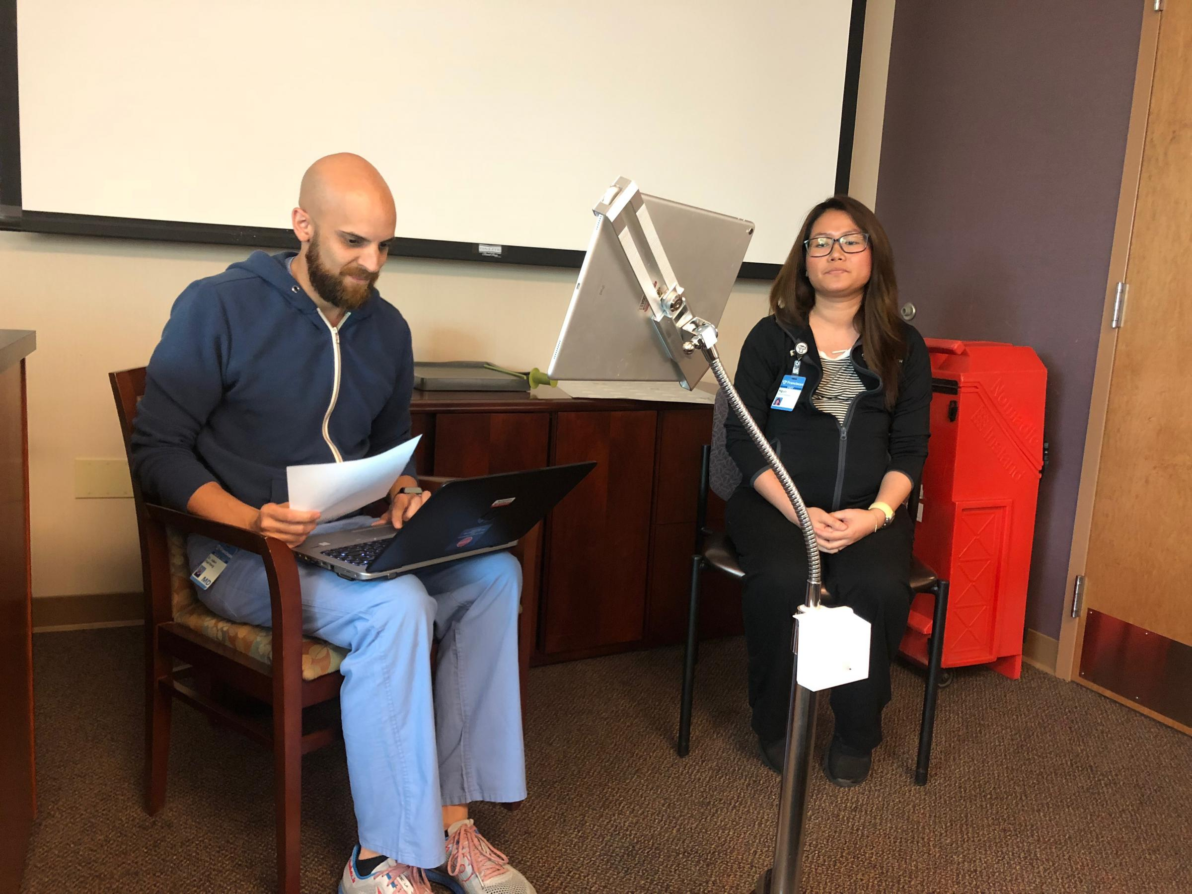 Caption: Adam Paarlberg (left) and medical assistant Ngun Tial (right) demonstrate how the live interpreter Martti system works., Credit: CARTER BARRETT/SIDE EFFECTS PUBLIC MEDIA.