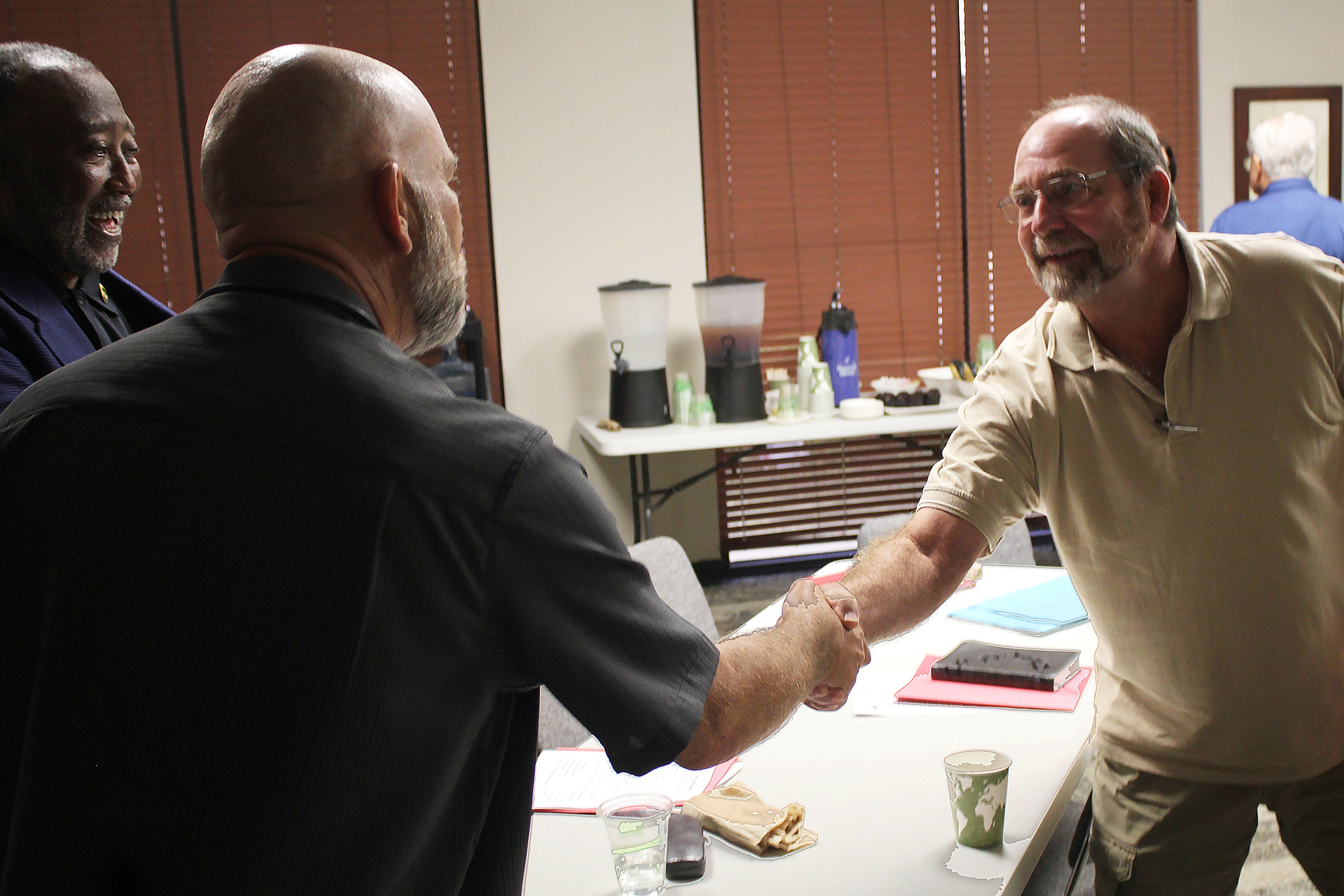 Caption: Mark George (right), a chaplain at the Caldwell County Jail in Lockhart, Tx., shakes hands with VA clergy training instructor Larry Collins, while attendee Vernon Cooper looks on., Credit: Carson Frame/American Homefront