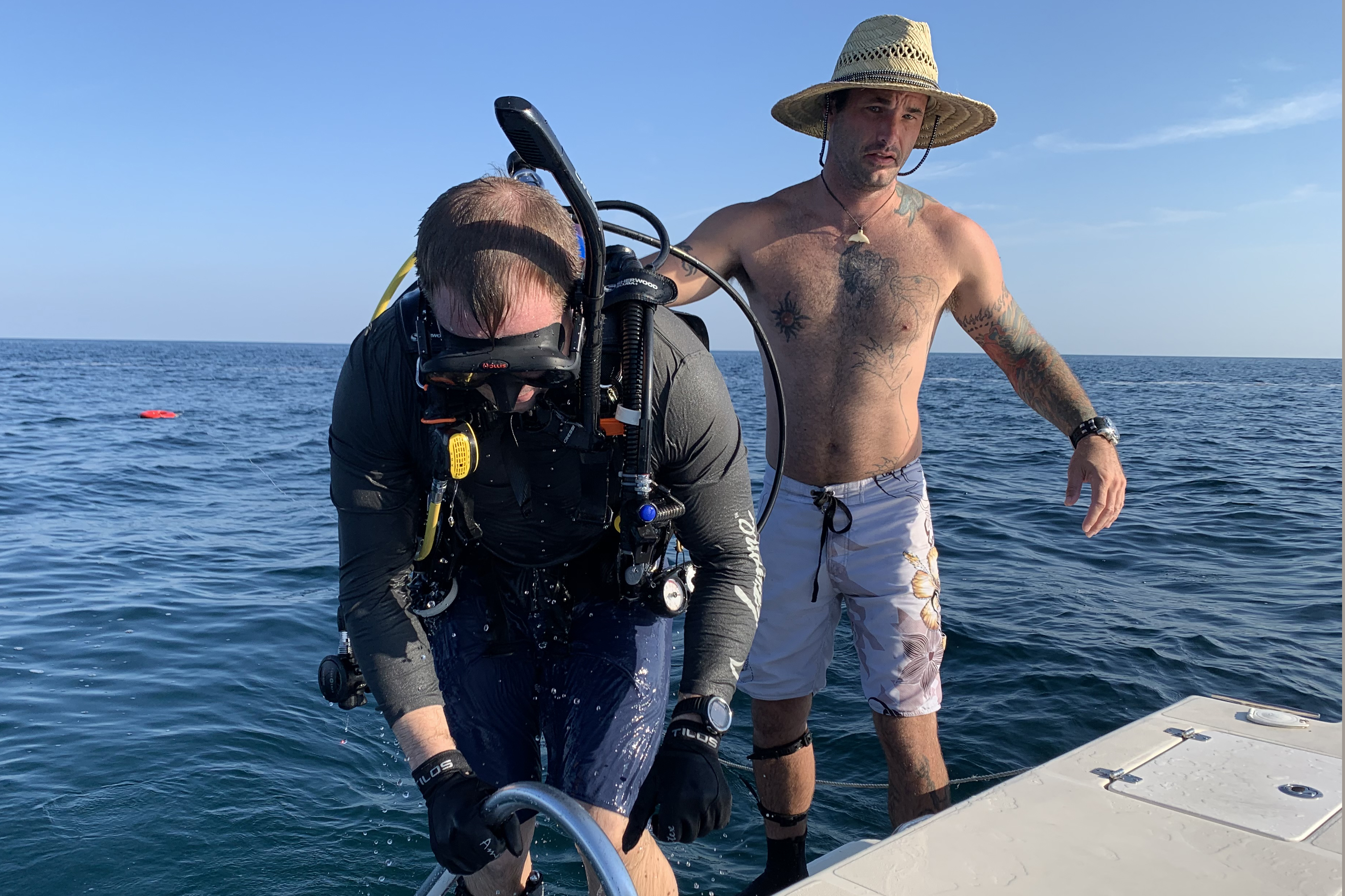Caption: Shawn Campbell helps Justin Herris get back on the boat after a dive at the Circle of Heroes military memorial off the coast of Clearwater, Fla., Credit: Stephanie Colombini/American Homefront