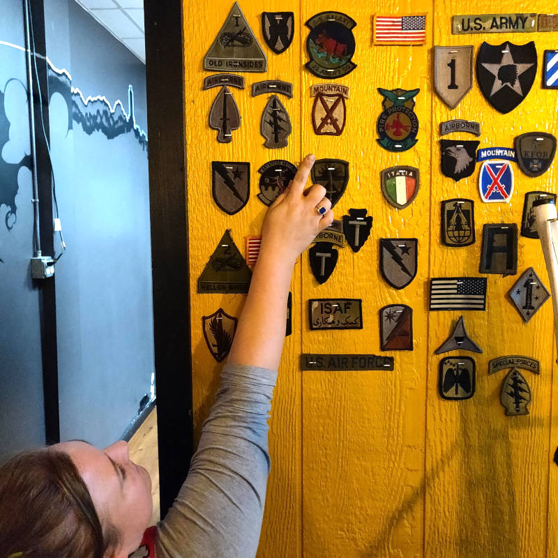 Caption: Wall of patches at Slab BBQ, including two for the 10th Mountain Division., Credit: Pios Labs