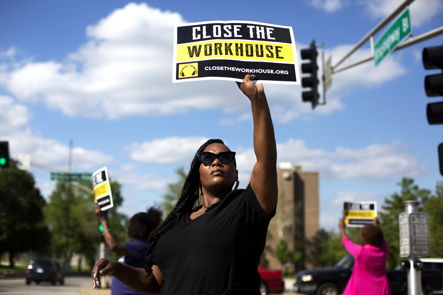 Caption: Inex Bordeaux holds up a sign while doing street outreach in north St. Louis to raise awareness about the Close the Workhouse campaign., Credit: Carolina Hidalgo