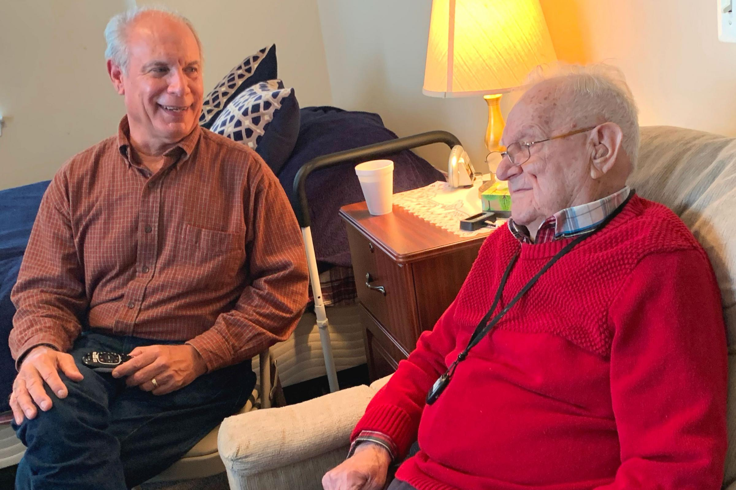 Caption: Gene Popiolek, 68, (left) visits his father Bernie, 95, at an assisted living facility outside Baltimore. Bernie, a WWII veteran, pays to live here with help from the VA's Aid and Attendance benefit., Credit: Stephanie Colombini / American Homefront