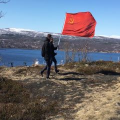 Caption: Two men carry a Soviet flag, Credit: Amy Martin