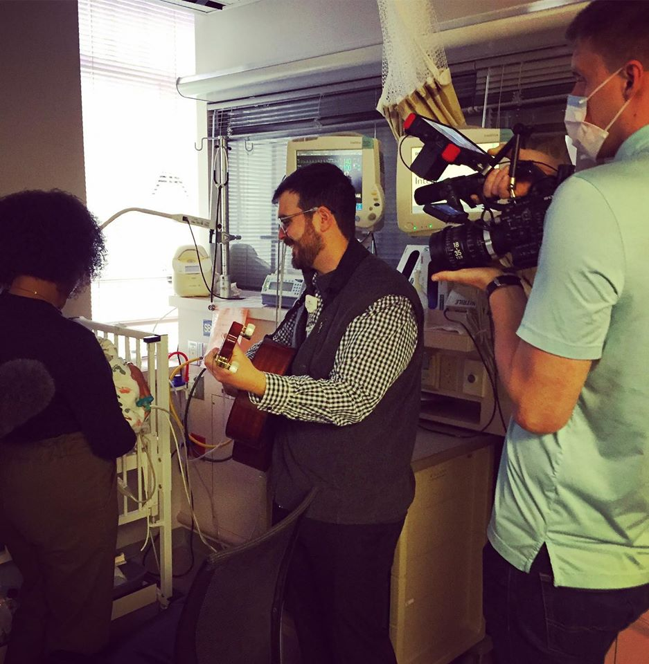 Caption: Music Therapist Chad Harmon with infant Jace Armstrong, Kendra Armstrong, Camera Op Spencer Greene, Credit: photo by Tony Morris 2020