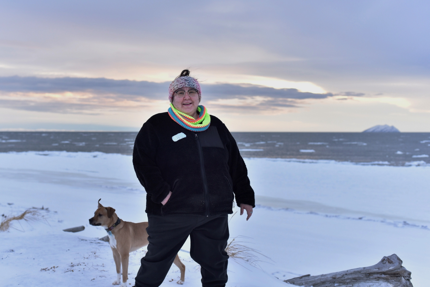 "Caption: Clarice ""Bun"" Hardy stands on the beach with her dog in the Native Village of Shaktoolik, Alaska. Hardy, a former 911 dispatcher for the Nome Police Department, says she moved back to her village after a sexual assault left her feeling unsafe in Nome. , Credit: AP Photo/Victoria Mckenzie"