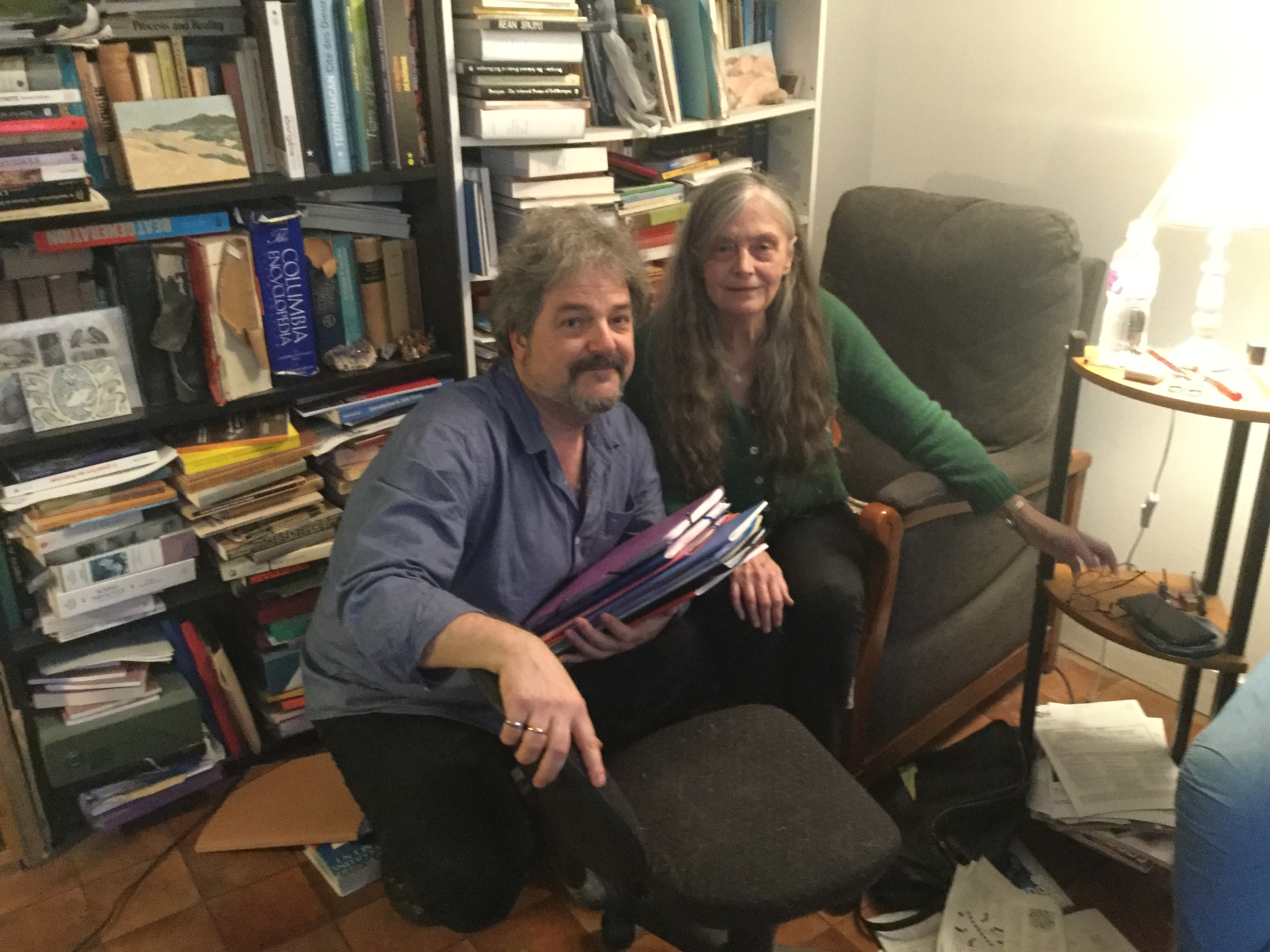 Caption: Poet alicce Notley and composer/poet Jeff Gburek in front of Alice's bookcase in Paris., Credit: Marjorie Van Halteren