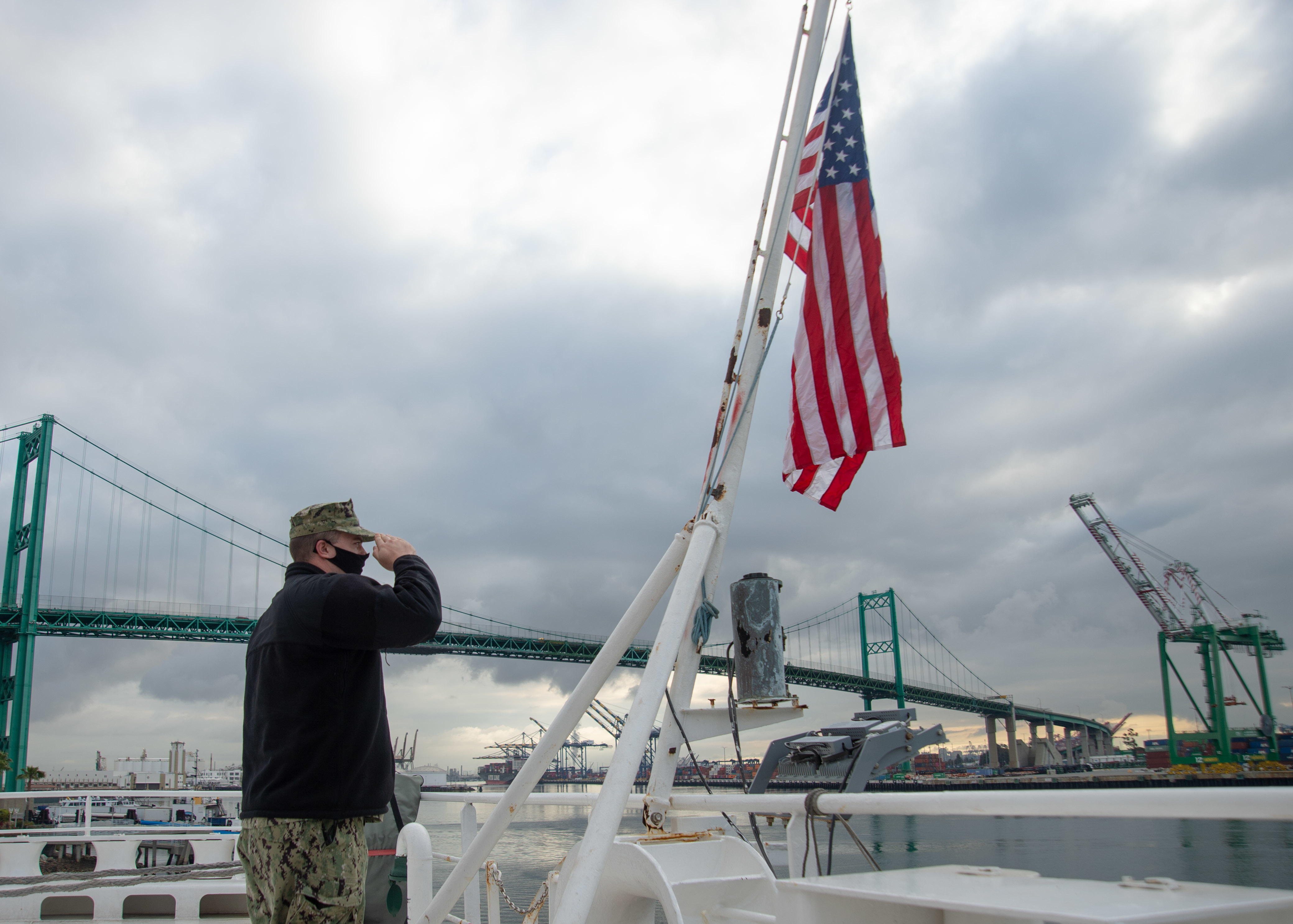Caption: Sailor John Arkulary from Marshfield, Wis. salutes the flag aboard the hospital ship USNS Mercy in Los Angeles April 13., Credit: Luke Cunningham / U.S. Navy