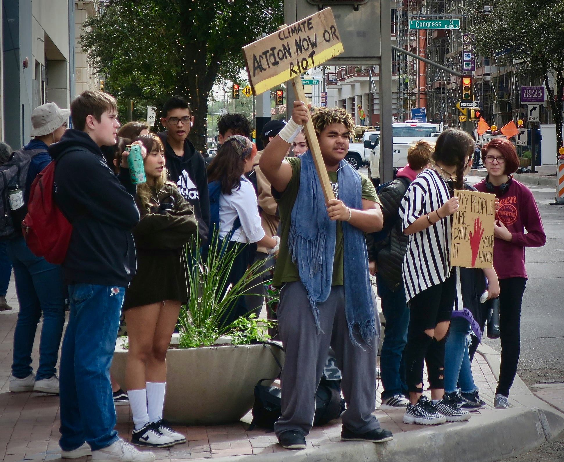 Caption: Cougar holds a sign at a climate protest, Credit: City High School
