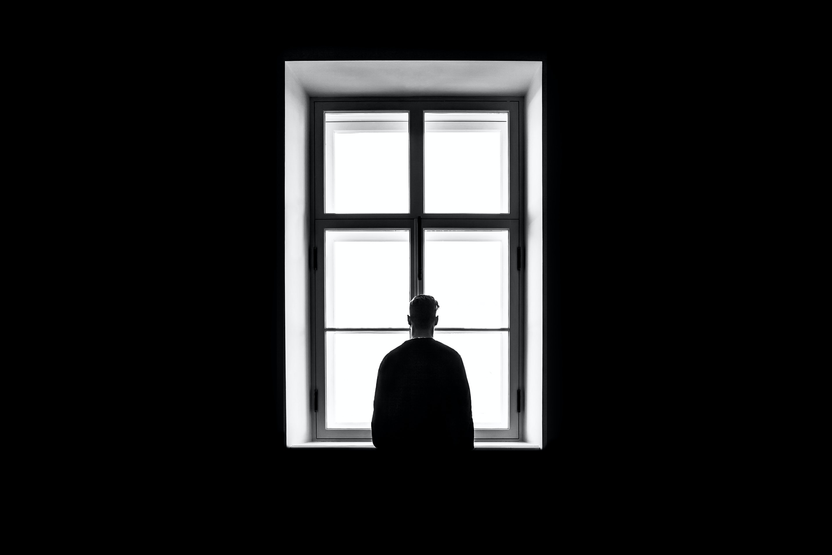 Caption: man standing in front of the window, Credit: Photo by Sasha Freemind on Unsplash
