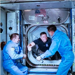 Caption: Astronaut Bob Behnken is welcomed aboard the International Space Station from his Crew Dragon spaceship., Credit: BILL STAFFORD / NASA - Johnson Space Center