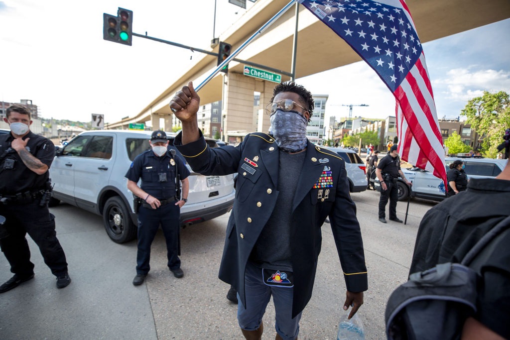 Caption: Aubrey Rose, an 18-year U.S. Army veteran, marches with an upside-down American flag over his shoulder in a protest against police violence in Denver., Credit:  Kevin J. Beaty / Denverite