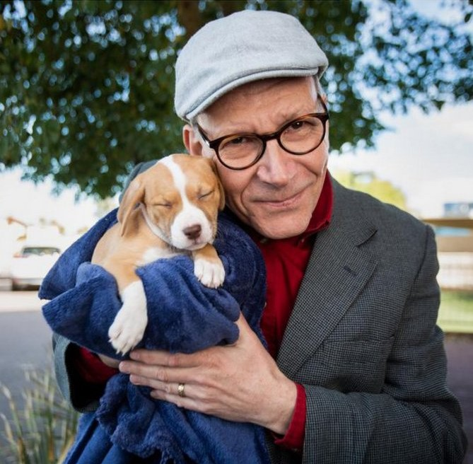 Caption: Clive Wynne, ASU professor of psychology, holding a puppy, Credit: Deanna Dent/ASU