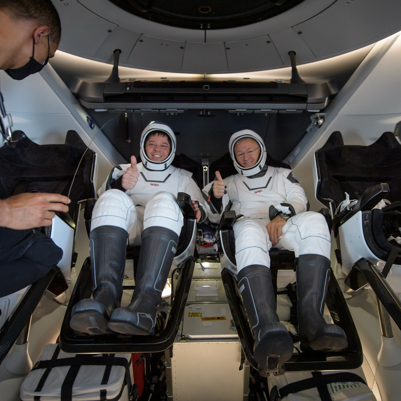 Caption: NASA astronauts Robert Behnken, left, and Douglas Hurley are seen inside the SpaceX Crew Dragon Endeavour spacecraft onboard the SpaceX GO Navigator recovery ship shortly after having landed in the Gulf of Mexico off the coast of Pensacola, Florida, Sunda, Credit: NASA/Bill Ingalls